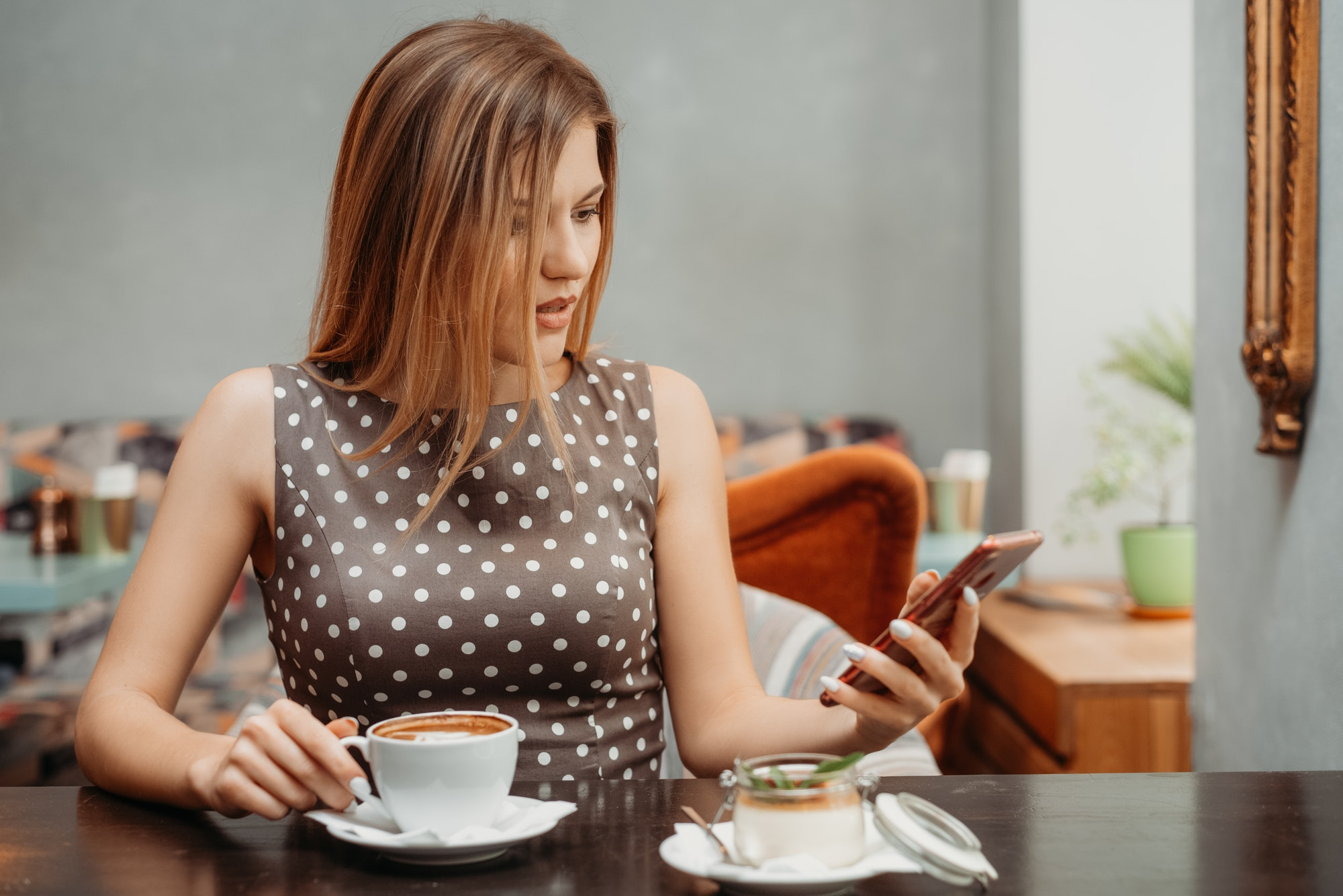Beautiful woman with amazed look using a mobile phone in cafe. Reading or SMS